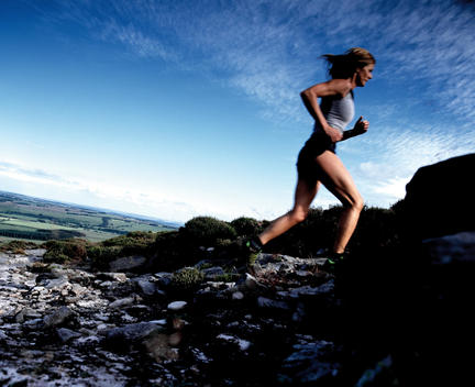 Woman Cross Country Running Through Hilly Landscape.
