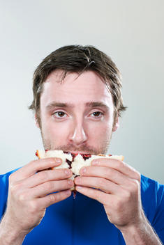 Jelly drips out of sandwich as the man takes a bite