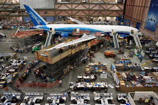 A view of the Boeing factory with its employees working on the production of an airplane