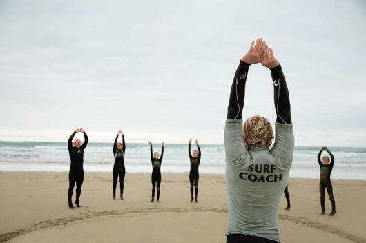 Back view of a surfing instructor and a group of students stretching their arms on a beach