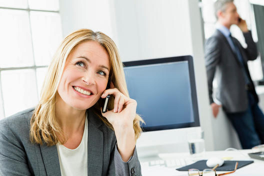 Germany, Businessman and woman talking on mobile phone, smiling