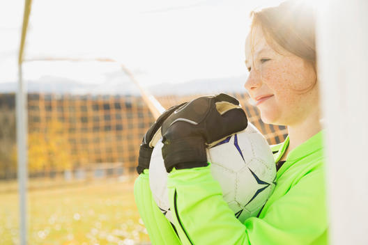 Goalie holding ball on soccer field