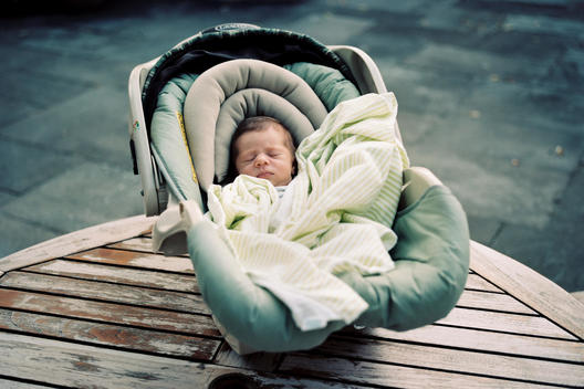 A baby sleeps in a car seat on a table.