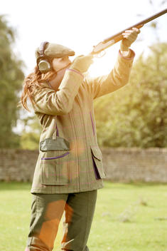 Lady in country clothing shooting traditional gun