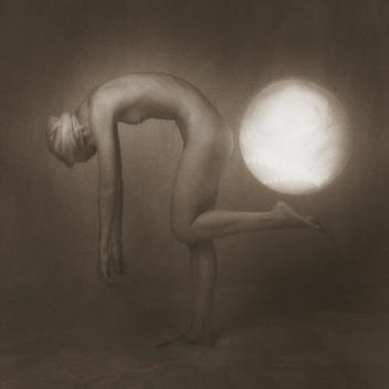 Anonymous, slender, nude woman bending from waist up with arms down and front leg uplifted as if supporting luminous lit globe