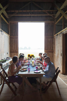 view of people eating at a wooden table inside a barn at Tom Colicchio\'s farm