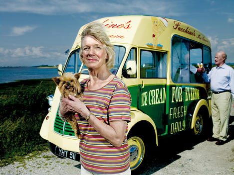 Portrait Of Mature Woman Holding Tiny Dog Next To Ice Cream Truck