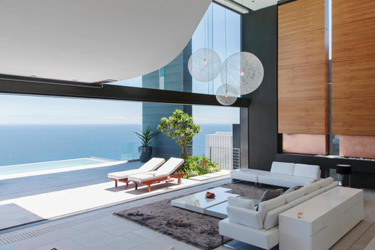 Living room and patio of modern house overlooking ocean