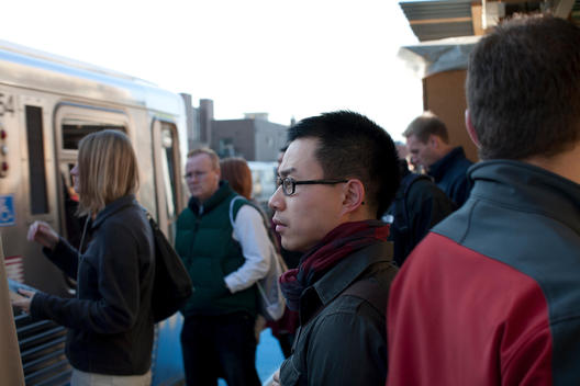 A Young Asian Man Waits Among A Crowded Cta Platform For His Train.
