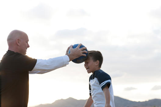 Coach Holding Ball And Boy Heading It