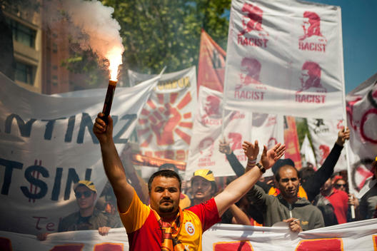 Turkish football team Galatasaray club fans wear their uniforms and fire the torch and shouting slogans against the current Islamist Government in the May 1st Labor day in Istanbul, Turkey.