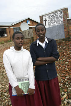 Ariane Rugumaho (16) on the left and Angeloda Umuhaza stand outside their school in Rwanda. The school has a satellite dish by a memorial to the 1994 genocide. School of the Assumption in Biramba, Rwanda, East Africa. African school. Attentive students. 1