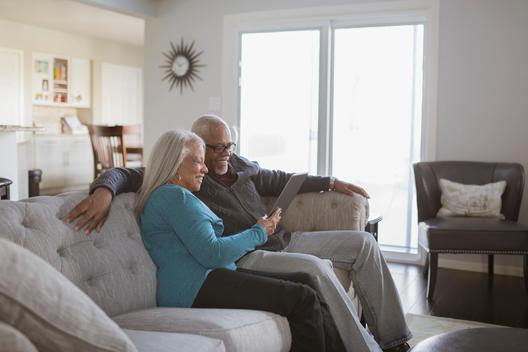 Older couple using digital tablet on sofa