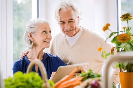 Senior couple using digital tablet whilst preparing food at kitchen counter