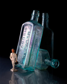 Still-Life Of Antique Metal Toy Doctor With Surgical Bag With Early 1900\'S Medicinal Bottles