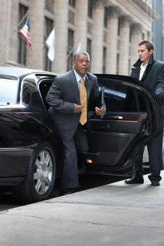 A Business Man Steps Onto A Chicago Street While His Chauffeur Holds The Car Door Open.