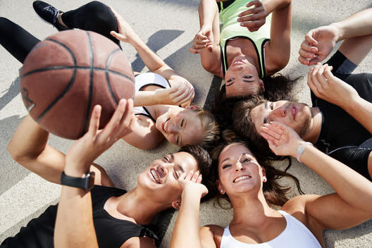 5 young people lying on floor, playing with basket ball
