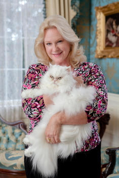 Ginger Hyland, present owner of The Towers, poses for a photograph with her cat in one of the many rooms.