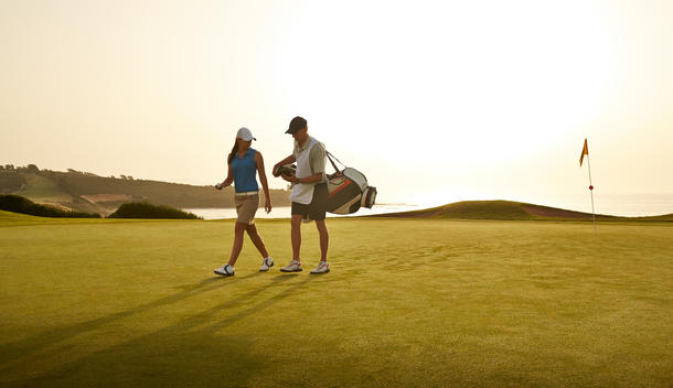 Caddy and woman walking on golf course overlooking ocean
