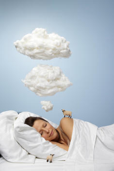 Woman sleeping with clouds overhead and toy sheep in the bed