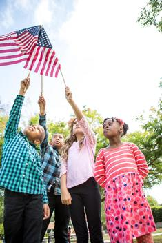 Children holding up American flags in park