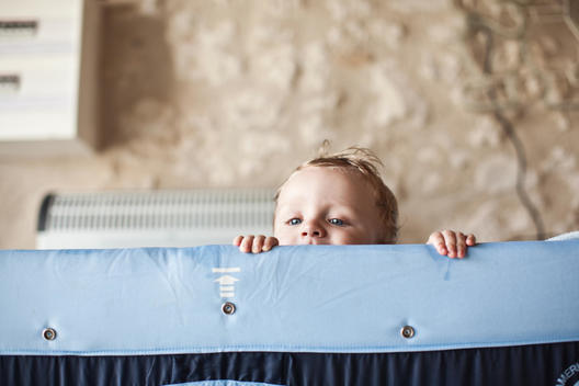 lifestyle baby peeking over crib
