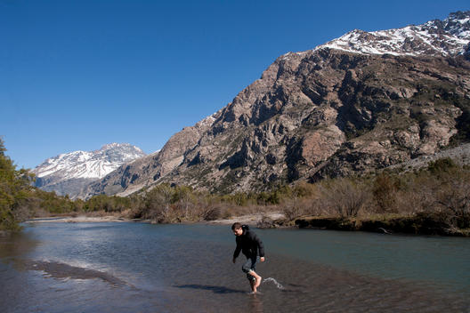 Man Crossing River In The Chilean Andes Mountains