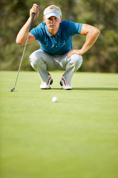 Man preparing to putt on golf course