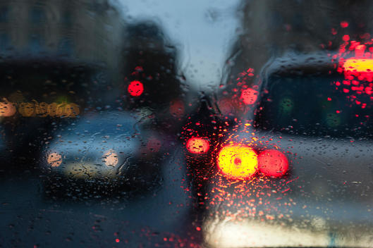 City traffic viewed through window during rain