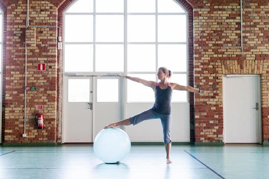 Full length of woman exercising with fitness ball in health club
