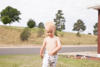 A young red-head boy struts through the front yard shirtless in pajama bottoms on a summer morning. Denver, CO