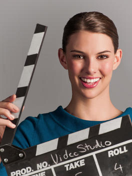 Young woman smiles at the camera as she holds a clap board.