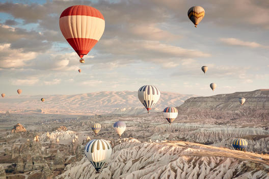 Large group of hot air balloons above flowing white canyon stone walls. The rising sun light hitting the peaks of hills and distant mountains,