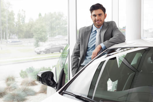 At the car dealer, Man standing at new car