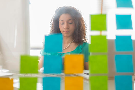 View through glass with post it notes of young female web designer at office desk