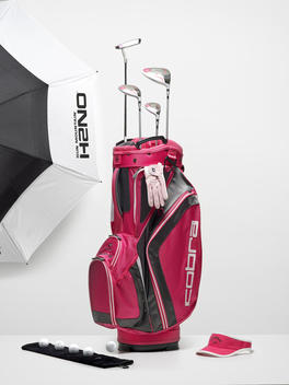 A golf bag surrounded by flying golf accessories.