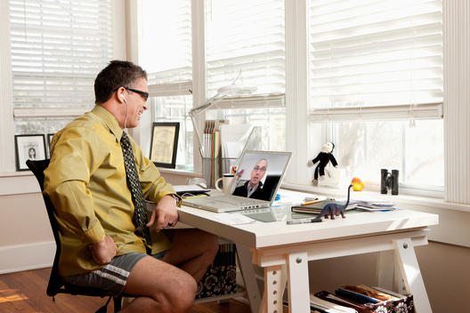 Hispanic businessman having video conference in shorts