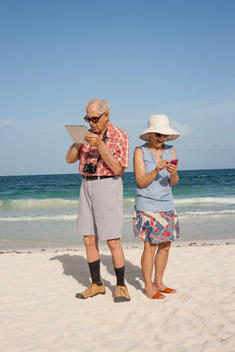 older couple using technology on the beach
