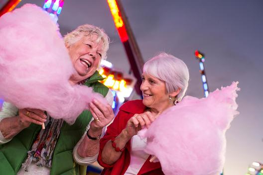 Two senior women eating candy-floss at fairground