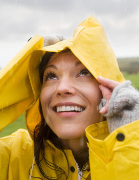 Hispanic woman wearing raincoat in rain