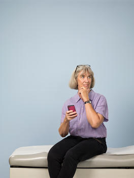App inventor Jeanne Pinder sits on a medical examination table holding her smart phone and her hand on her chin