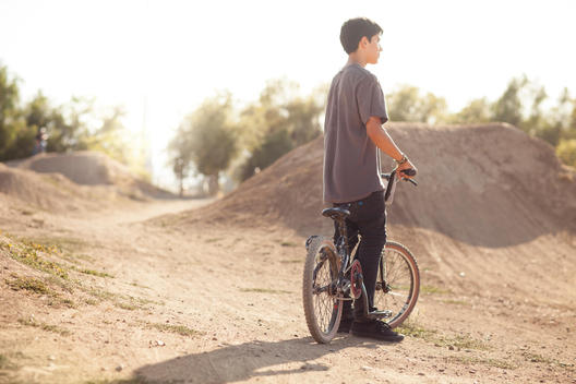 Tween Boy at a BMX race track looking off into the distance