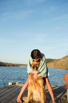A girl cuddling a golden retriever dog.