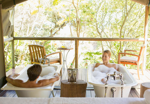 Couple in twin bathtubs in outdoor spa