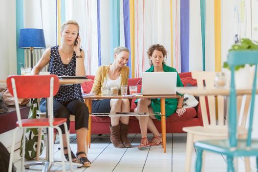 Full length of women using technologies in coffee shop