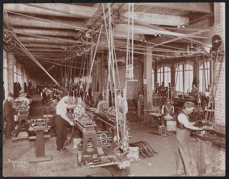 Automobile Factory At Kingsland Point, Hudson River (Near Tarrytown, Ny). Rows Of Work Stations In Machine Shop With Steam-Powered, Belt-Driven Machinery And Laborers.