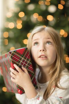Christmas morning themed portrait of a young girl shaking a present, trying to determine what might be inside.