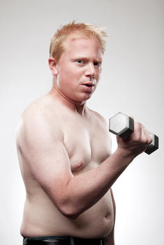 Young out of shape shirtless man holding dumbbell.