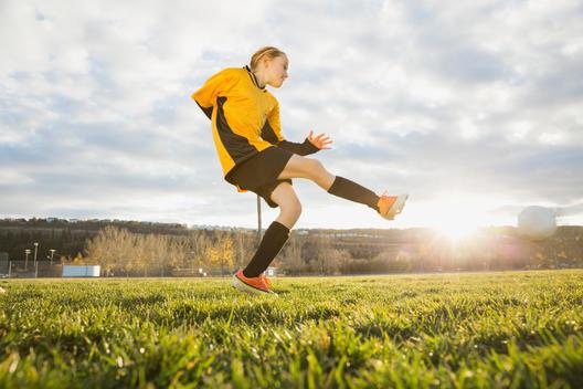 Soccer player kicking ball on field