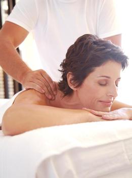 Massage therapist massaging woman on shoulders outdoors